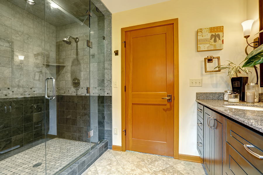 Modern bathroom interior with glass door shower and tile wall trim. Bathroom with bright orange door